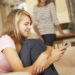 Teenage Girl Sitting On Sofa At Home Texting On Mobile Phone With Mother In Background